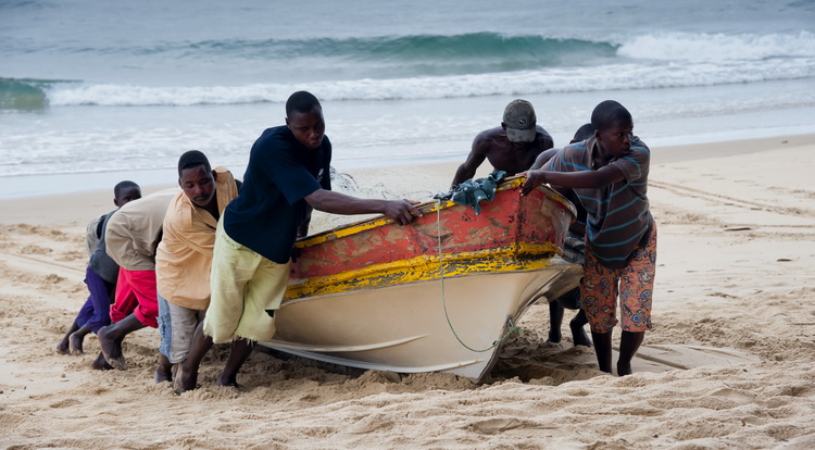 Tofo Death on the Beach - Local fishermen help to haul their boat up Tofo beach